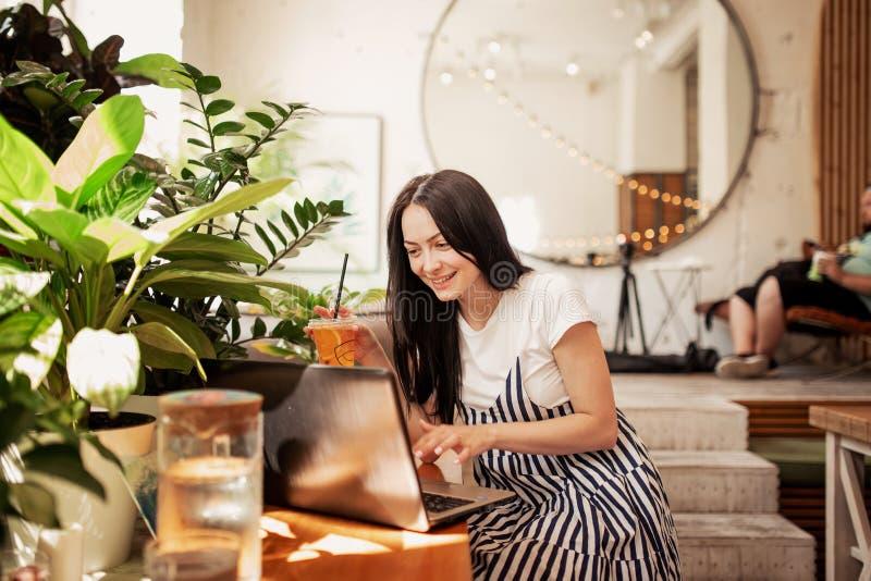Uma menina magro nova bonita com cabelo escuro e vidros, vestidos no estilo ocasional, senta-se na tabela com um portátil em um n foto de stock