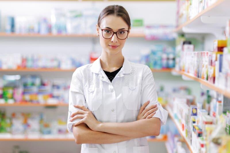 Uma menina magro nova com cabelo escuro longo e os vidros, vestindo um revestimento branco, está seguramente por prateleiras em u imagem de stock