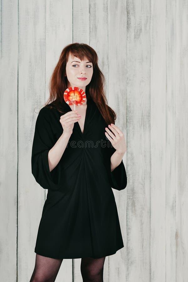 Uma menina moreno bonita no vestido preto com pirulito vermelho fotos de stock