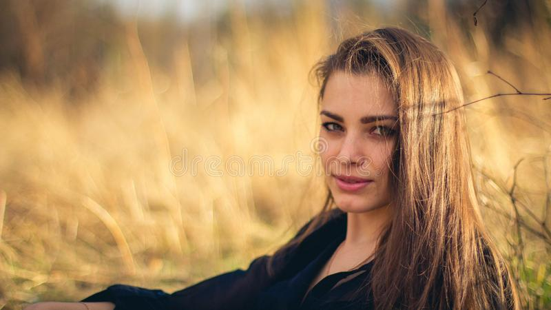 Uma menina moreno bonita que levanta em um campo no outono Foto da arte imagem de stock royalty free