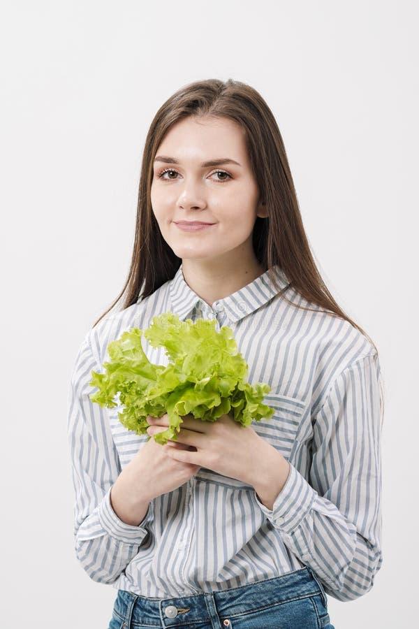 Uma menina moreno delgada com cabelo longo em um fundo branco, realiza em suas mãos e mostra as folhas de fresco verde fotos de stock royalty free