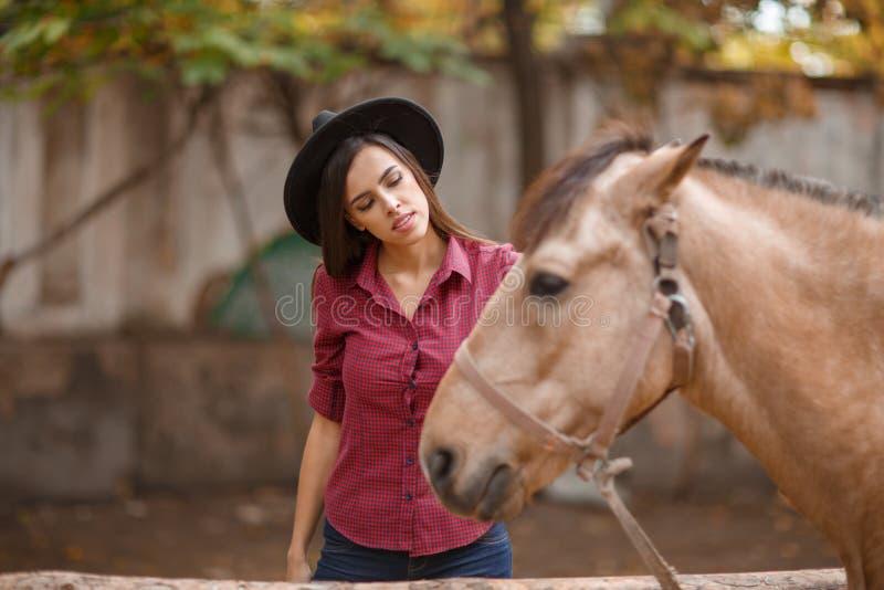 Uma menina moreno em um chapéu olha um cavalo foto de stock royalty free