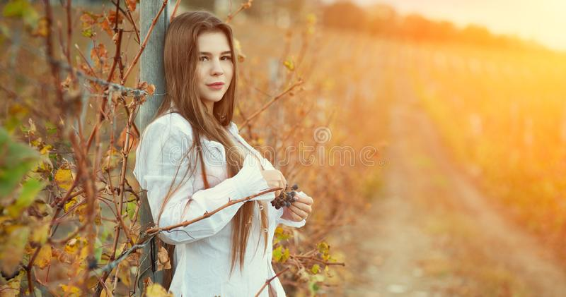 Uma menina moreno semi-nua em uma blusa branca do vintage e em um cabelo longo que levantam na perspectiva de um vinhedo do outon foto de stock