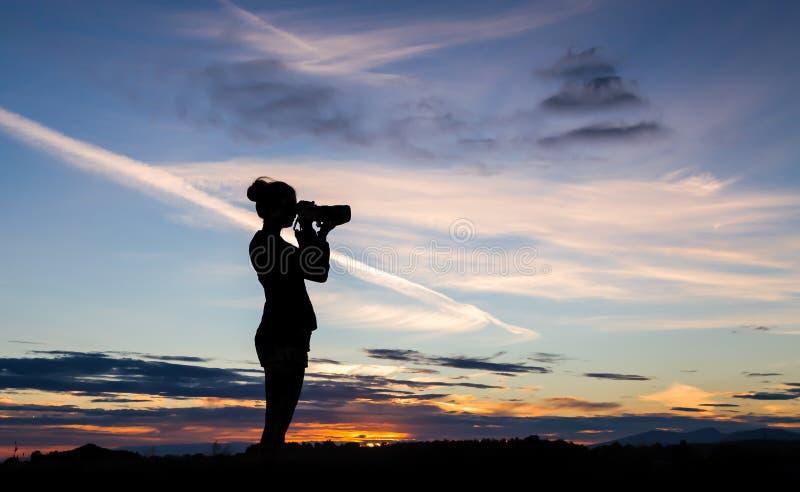 Uma menina mostrada em silhueta contra um céu do por do sol, tomando uma foto com um DSLR imagens de stock royalty free