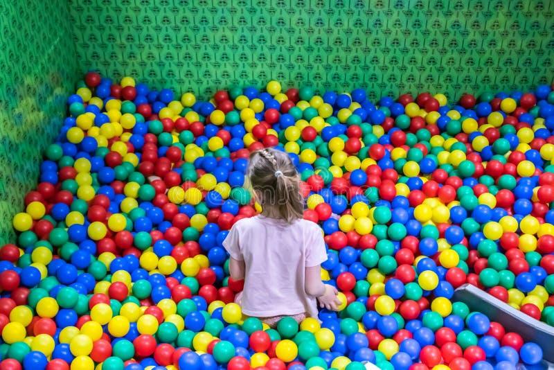 Uma menina na associação com muitas bolas coloridas nas crianças que jogam a sala imagem de stock