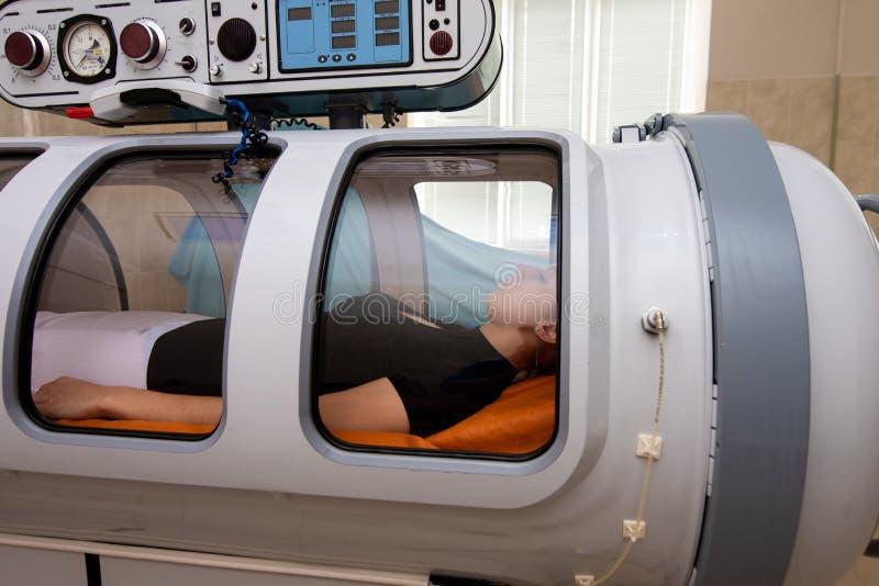 Uma menina na câmara hyperbaric fotos de stock
