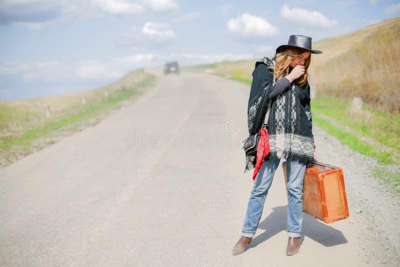 Uma menina na calças de ganga, um poncho, um chapéu de couro preto com uma mala de viagem marrom velha em suas mãos está na estra imagens de stock