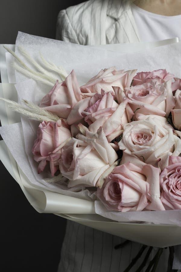 Uma menina na roupa branca está guardando um ramalhete bonito delicado de rosas cor-de-rosa, em um pacote translúcido fotos de stock