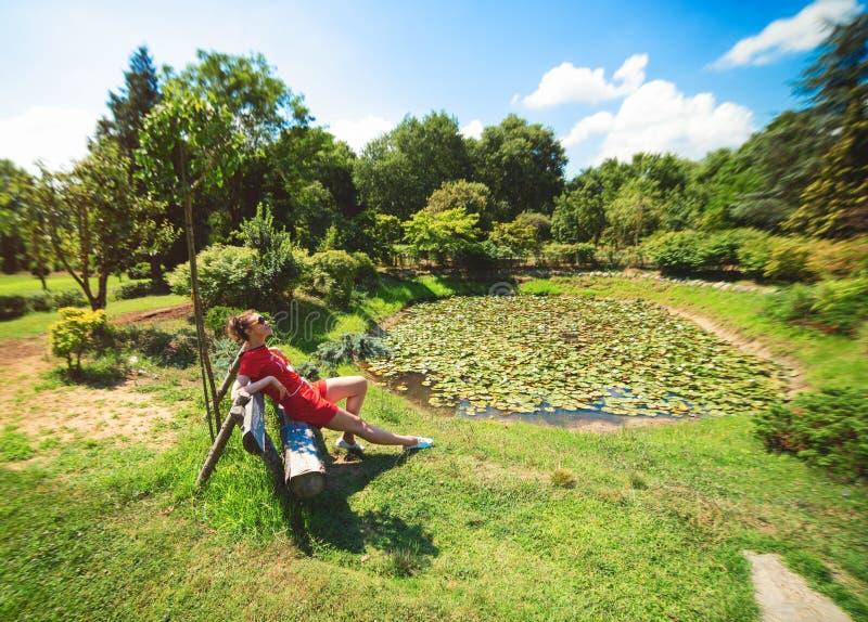 Uma menina no assento vermelho em pouca lagoa com os lírios de água no arboreto de Karaca fotografia de stock