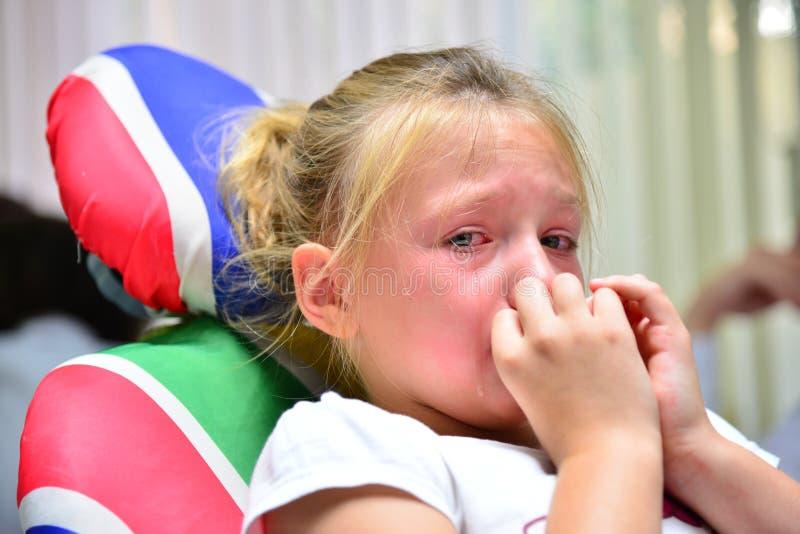 Uma menina no dentista está gritando com rasgos em uma nomeação do ` s do doutor ao tratar um dente imagem de stock