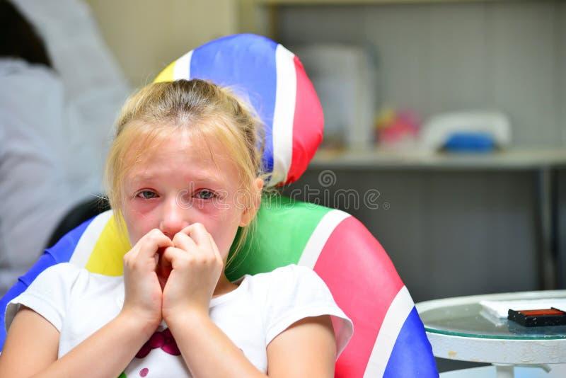 Uma menina no dentista está gritando com rasgos em uma nomeação do ` s do doutor ao tratar um dente fotografia de stock