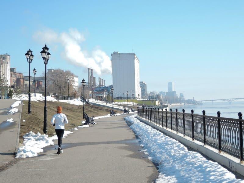 Uma menina no os esportes que brancos o uniforme é contratado na corrida, ela corre ao longo do litoral da mola em um dia de mola imagem de stock