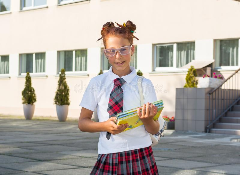 Uma menina no uniforme com um penteado engraçado com lápis coloridos dentro ele imagem de stock