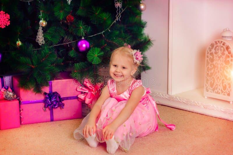 Uma menina no vestido cor-de-rosa no Natal imagem de stock