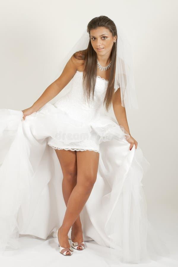 Uma menina no vestido de casamento mostra-lhe os pés fotografia de stock