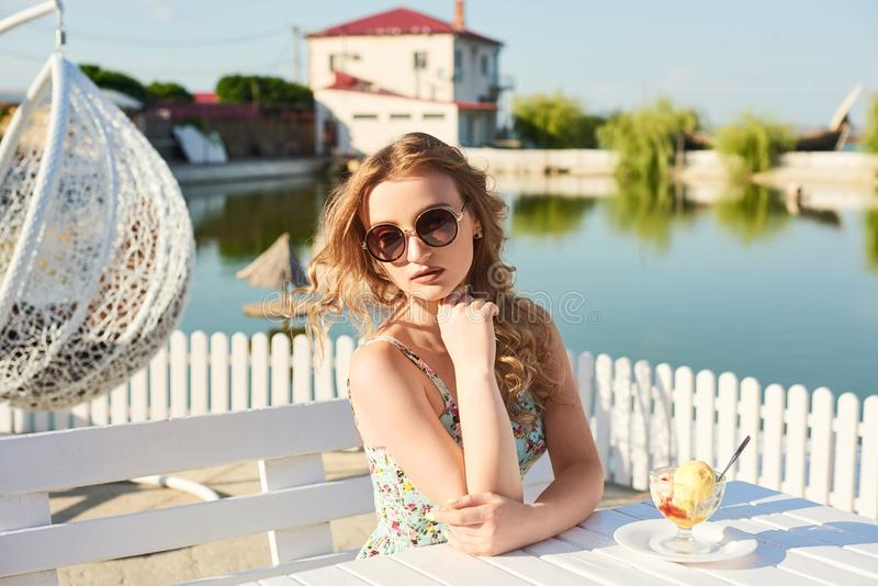 Uma menina no vestido do verão que come um gelado foto de stock royalty free