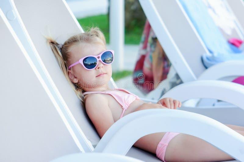 Uma menina nos óculos de sol toma sol em uma cadeira de plataforma Um bebê bonito está descansando foto de stock