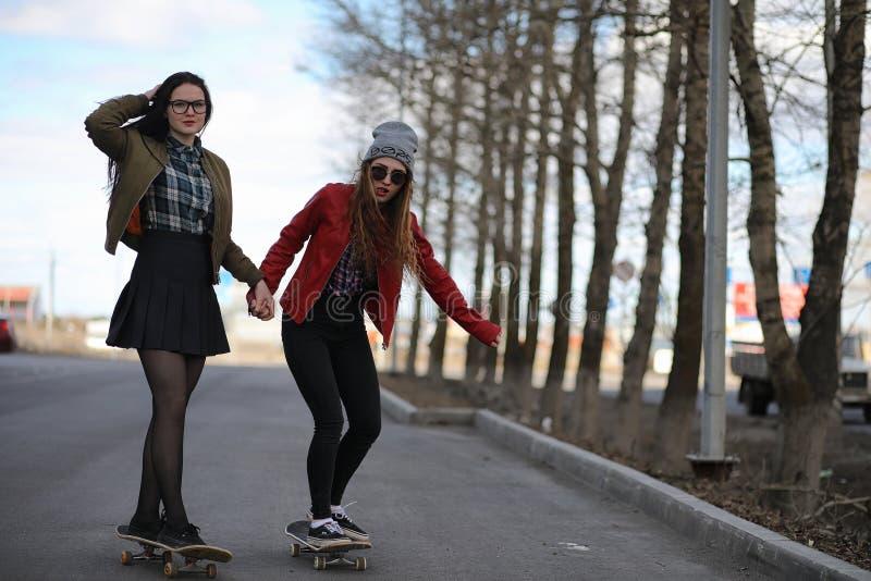 Uma menina nova do moderno está montando um skate Amigas f das meninas foto de stock royalty free