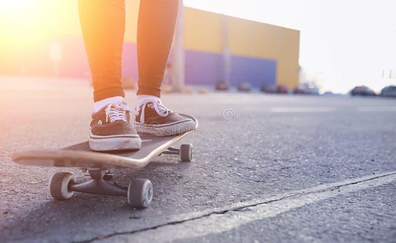 Uma menina nova do moderno está montando um skate Amigas f das meninas imagem de stock