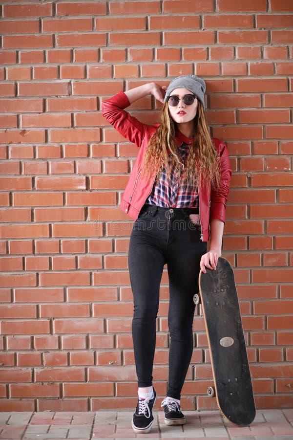 Uma menina nova do moderno está montando um skate Amigas f das meninas imagens de stock