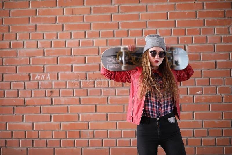 Uma menina nova do moderno está montando um skate Amigas f das meninas fotografia de stock royalty free