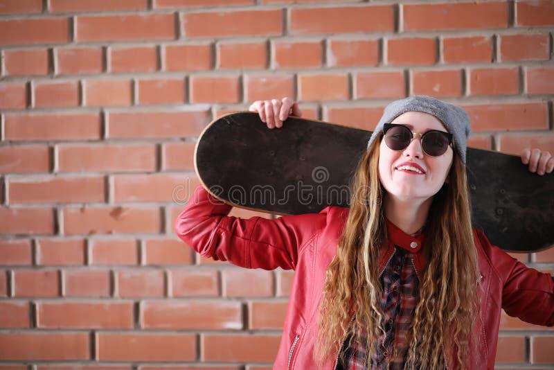 Uma menina nova do moderno está montando um skate Amigas f das meninas fotos de stock