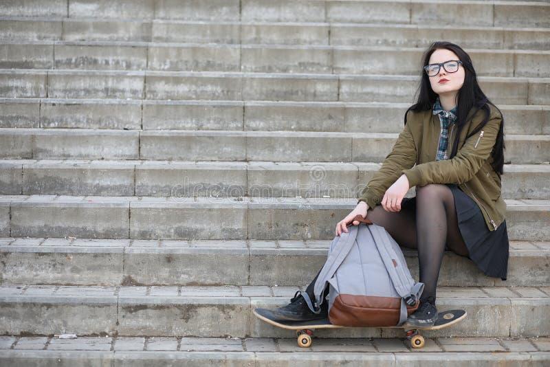 Uma menina nova do moderno está montando um skate Amigas f das meninas fotografia de stock