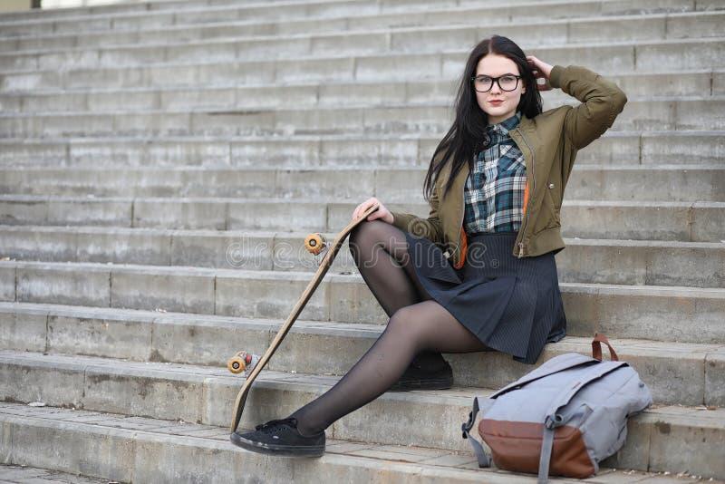 Uma menina nova do moderno está montando um skate Amigas f das meninas imagem de stock royalty free