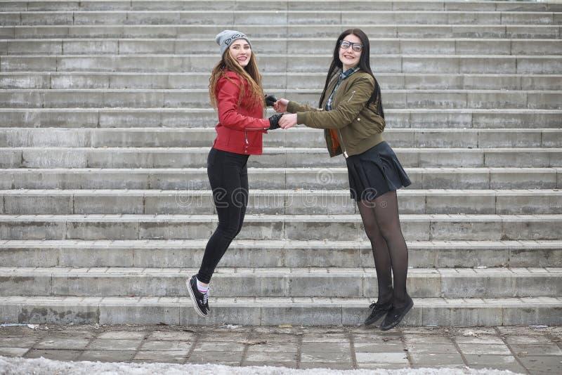 Uma menina nova do moderno está montando um skate Amigas f das meninas foto de stock