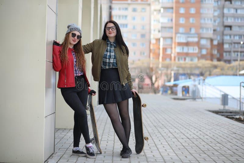 Uma menina nova do moderno está montando um skate Amigas f das meninas imagens de stock royalty free