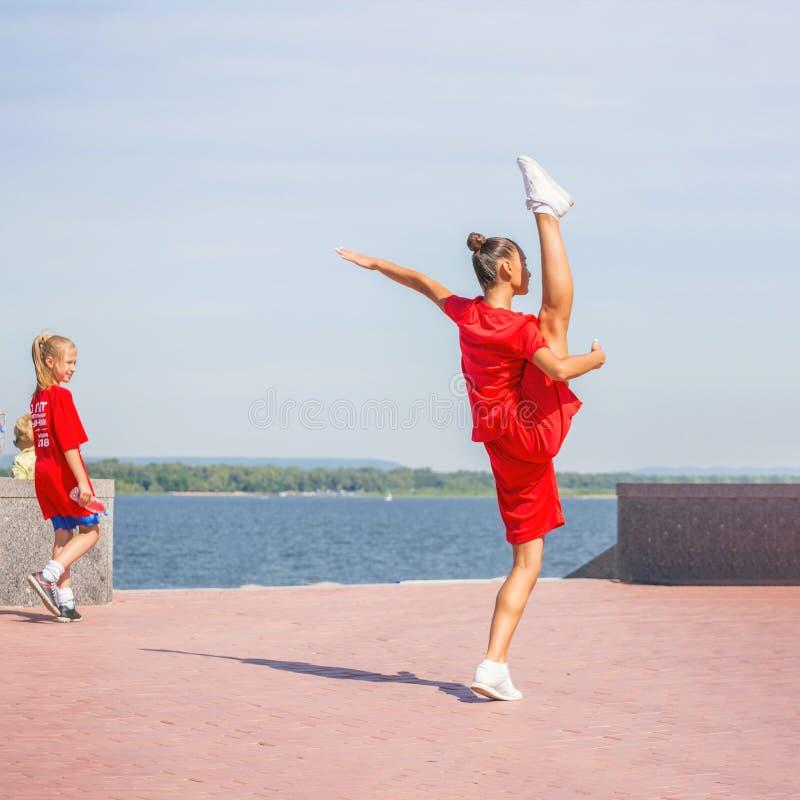 Uma menina olha uma ginasta bonita durante um feriado na terraplenagem do Rio Volga em um dia de verão quente fotografia de stock