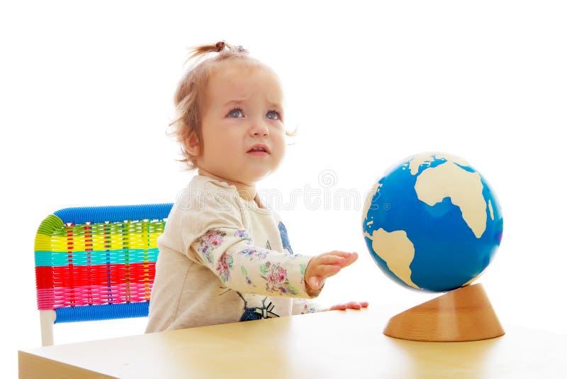 Uma menina olha o globo imagem de stock