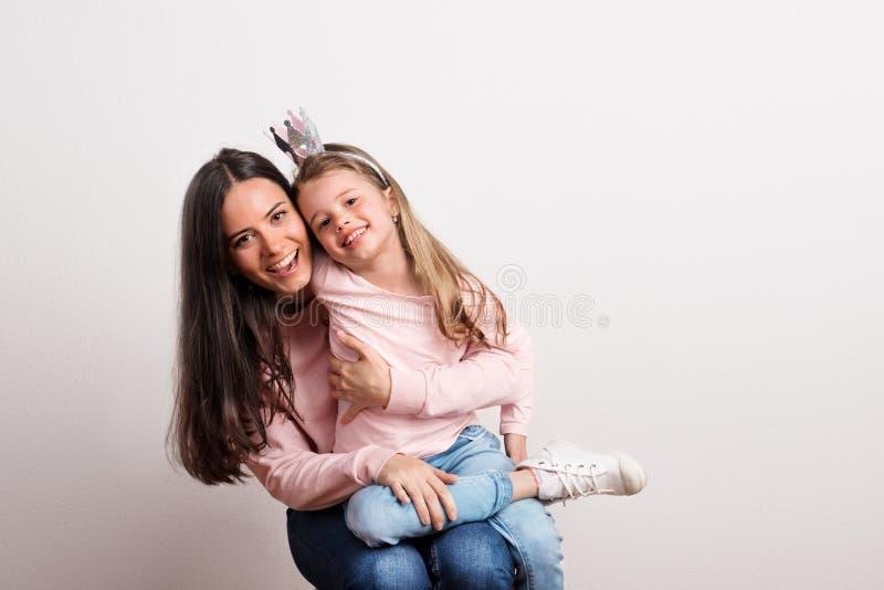 Uma menina pequena com faixa da coroa e sua mãe que senta-se em um estúdio fotos de stock royalty free