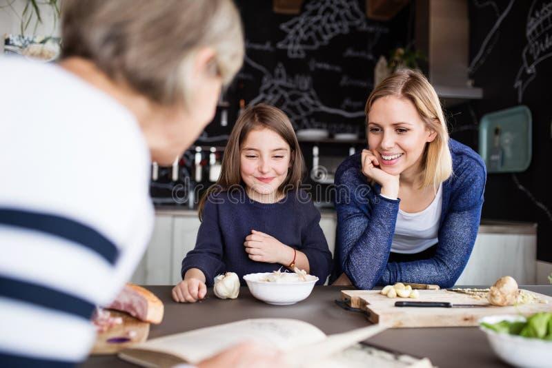 Uma menina pequena com mãe e avó em casa imagens de stock