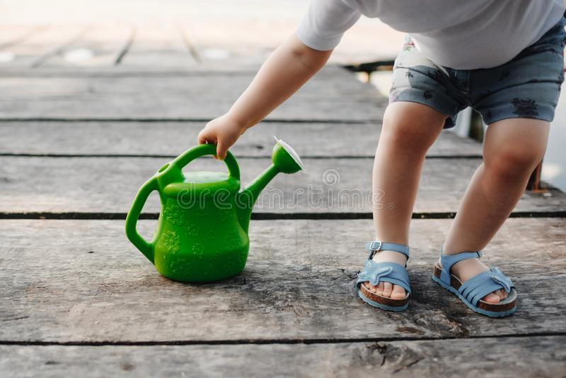 Uma menina pequena está jogando com uma lata molhando de uma ponte de madeira Mola e verão Jardinagem Lata molhando verde imagens de stock royalty free