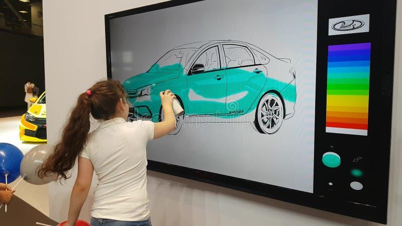 Uma menina pinta um carro em um whiteboard interativo imagens de stock