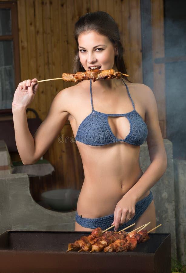 Uma menina prepara a carne foto de stock