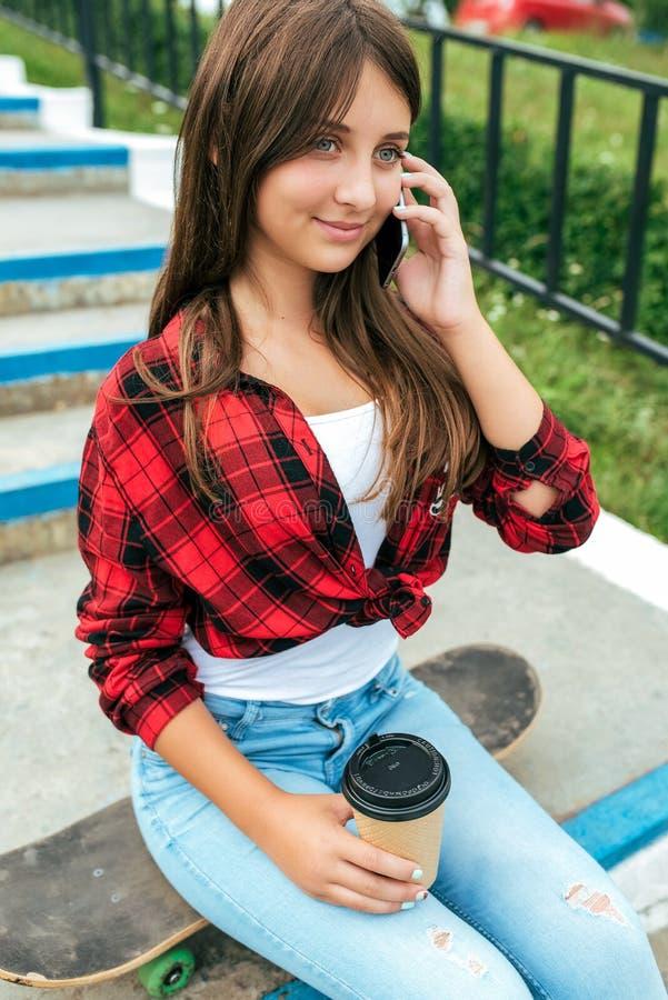 Uma menina que chama o telefone celular uma estudante moreno que senta-se no verão na cidade no fundo das etapas Uma comunicação  imagens de stock royalty free