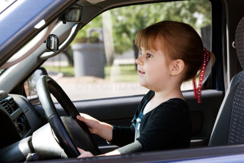 Uma menina que conduz um carro fotografia de stock