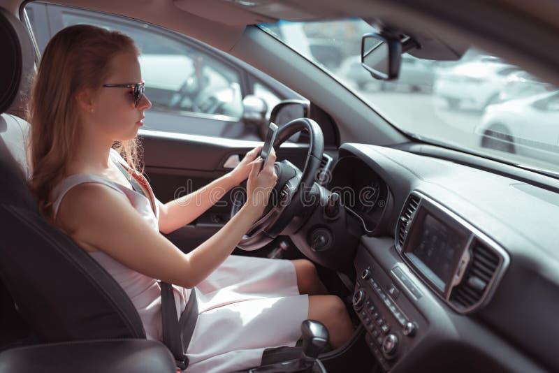 Uma menina que conduz um carro lê e escreve uma mensagem no telefone, uma candidatura online, estacionando na loja, esperando no fotografia de stock
