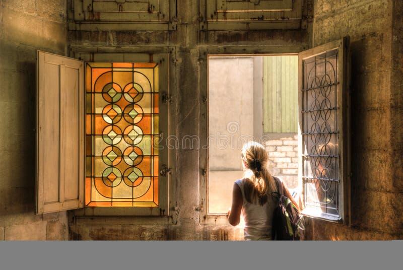 Uma menina que enfrenta perto de um indicador de vidro manchado imagens de stock royalty free