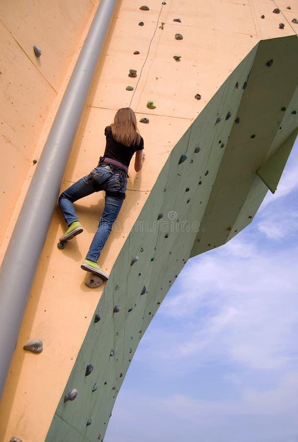Uma menina que escala à parte superior da parede imagem de stock royalty free