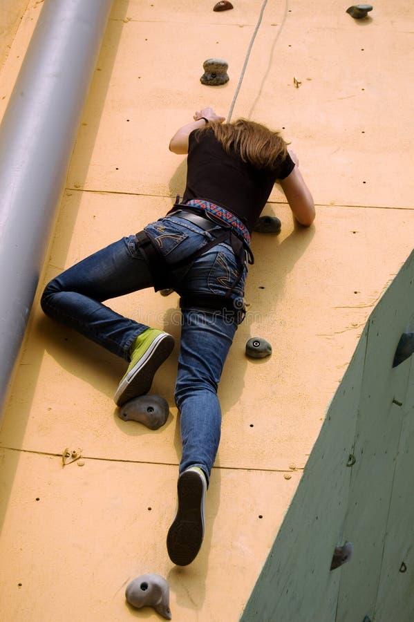 Uma menina que escala à parte superior da parede fotos de stock royalty free