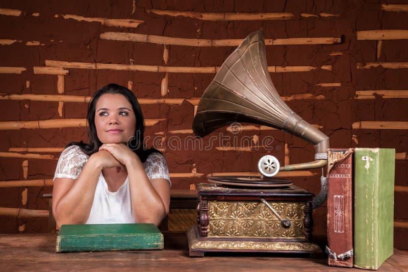 Uma menina que escuta a música em um gramofone velho fotos de stock