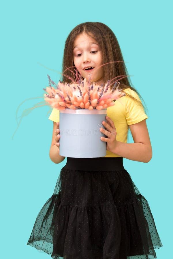 Uma menina que guarda flores A criança foi dada um presente Fundo para um cart?o do convite ou umas felicita??es foto de stock royalty free