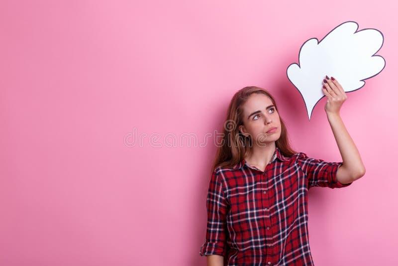 Uma menina que guarda uma imagem de papel de um pensamento ou de uma ideia aéreo olhando a e olhando acima Em um fundo cor-de-ros imagens de stock royalty free