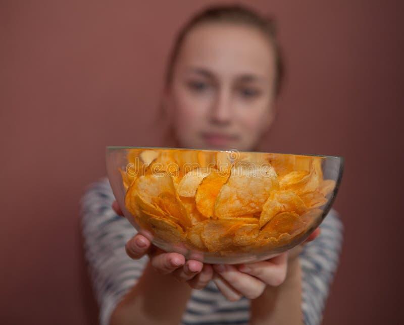 Uma menina que guarda a placa grande com microplaquetas de batata rola Perguntando a comer junto, felicidade que compartilha do c fotografia de stock