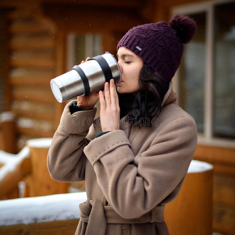 Uma menina que guarda uma garrafa térmica com uma bebida quente Uma caneca de café em suas mãos A aleia do inverno na cidade, uma fotos de stock royalty free
