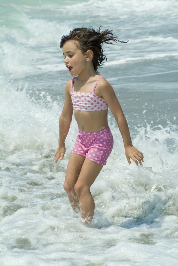 Uma menina que joga no mar foto de stock royalty free