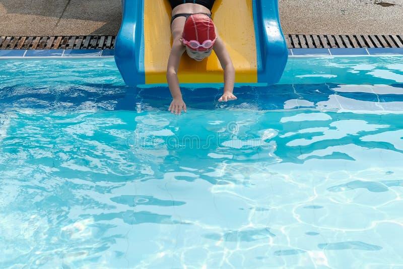 uma menina que joga o slider na associação do swimmimg fotos de stock